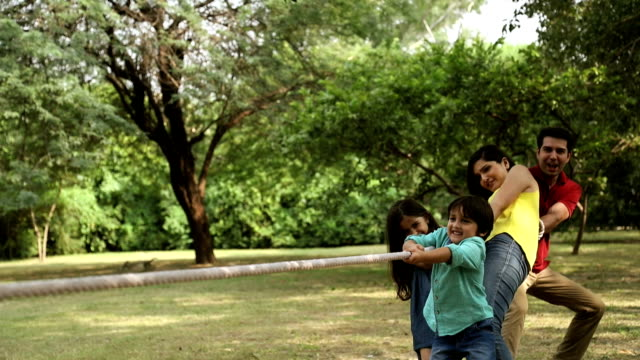 Family playing tug of war in park, Delhi, India