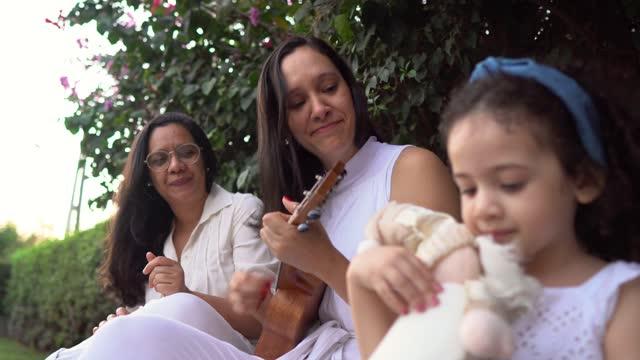 vidéos et rushes de famille jouant l'ukulélé et chantant à l'extérieur - tante