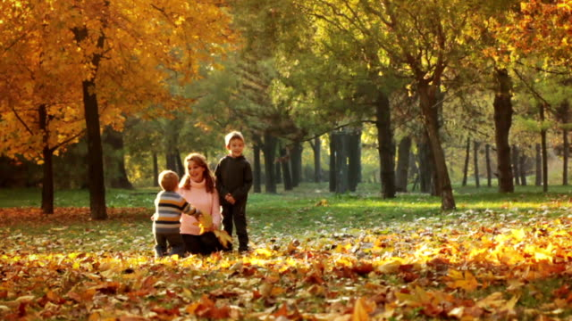 Family playing with autumn leaves