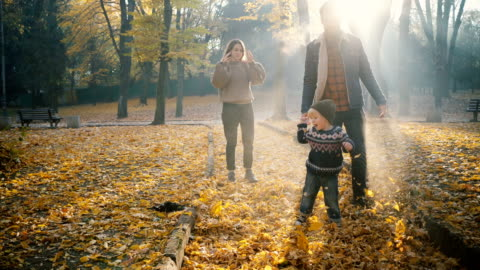 stockvideo's en b-roll-footage met familie spelen met zoontje in park in het najaar - autumn
