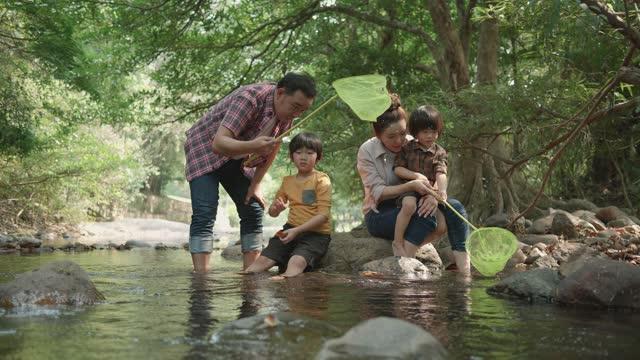 vidéos et rushes de famille jouant avec des filets dans le flux - activité de plein air