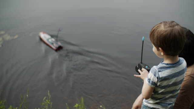 family playing with remote-controlled boat - nautical vessel stock videos & royalty-free footage