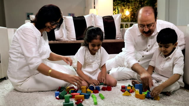 Family playing with toys in the home, Delhi, India