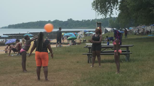 family plays catch at the beach at gunpowder state falls on may 22, 2021 in middle river maryland. nearly 6 000 covid-19 vaccine shots have been... - maryland us state stock videos & royalty-free footage