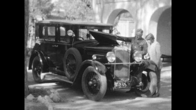 family plays with dog outside their house, people inspecting and cleaning 1930's vauxhall sedan. from a home movie of a car journey from pindi to... - colonial stock videos & royalty-free footage