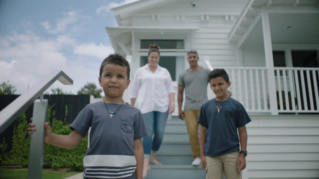 family pose on the front steps of their new home - new zealand stock videos & royalty-free footage