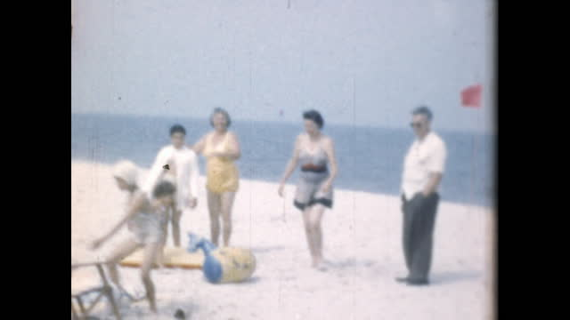 family poses together on the beach; the mother puts an innertube around her daughter. - 水泳用浮き輪点の映像素材/bロール