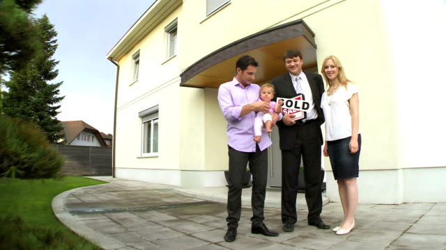 HD CRANE: Family Posing In Front Of Their New Home