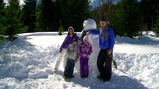 hd crane: family posing with a snowman - crane shot stock videos & royalty-free footage