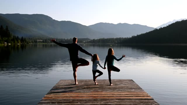 family practising yoga outdoors - mindfulness stock videos & royalty-free footage