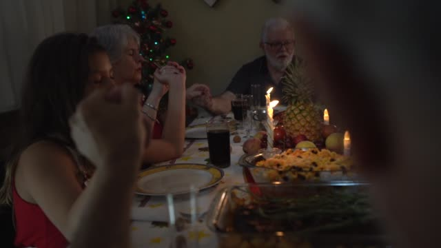 Familie zu beten, bevor zu einem Abendessen zusammen - Weihnachtszeit