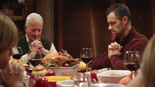 Family praying before Thanksgiving dinner