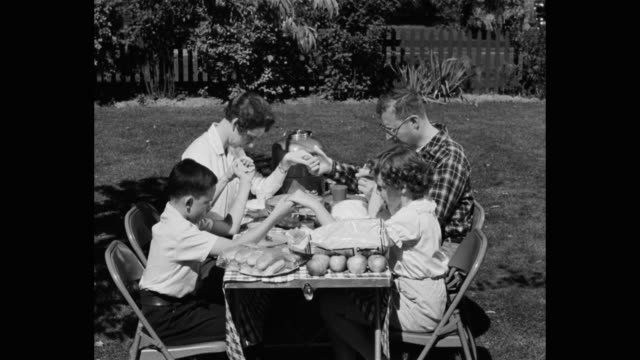 family praying together before eating at picnic table in backyard - praying stock videos & royalty-free footage
