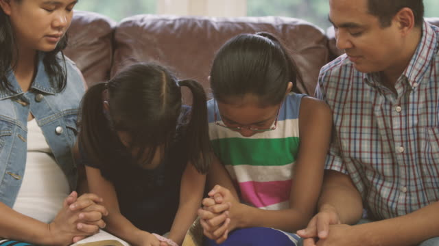 family praying together during devotionals - bible stock videos & royalty-free footage