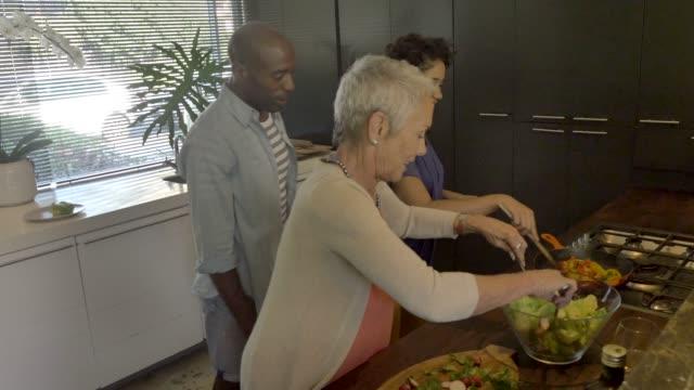 vídeos y material grabado en eventos de stock de family preparing food during reunion at home - de descendencia mixta