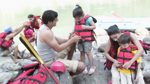 family preparing for river rafting  - life jacket stock videos & royalty-free footage