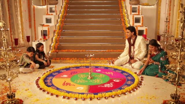 Family preparing rangoli in diwali festival