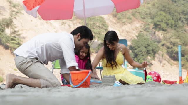 Family preparing sandcastle at riverbank