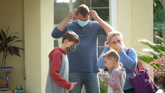 family putting on face masks as they leave home - 8 9 years stock videos & royalty-free footage