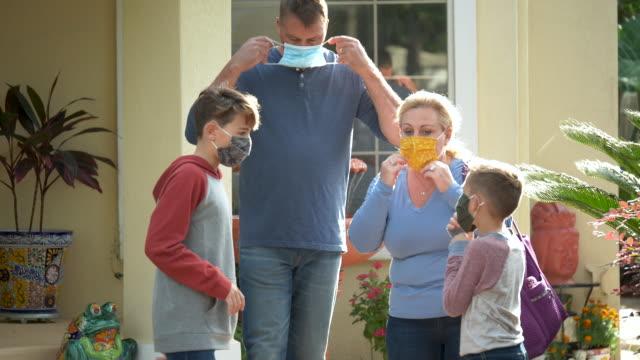 familie setzt gesichtsmasken auf, wenn sie das haus verlassen - 50 54 years stock-videos und b-roll-filmmaterial