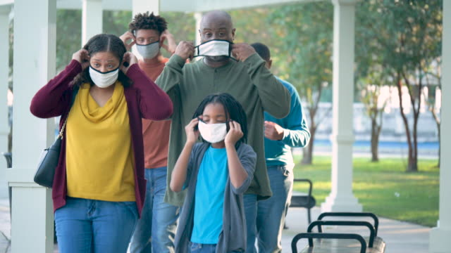 family putting on face masks during covid-19 pandemic - 16 17 years stock videos & royalty-free footage