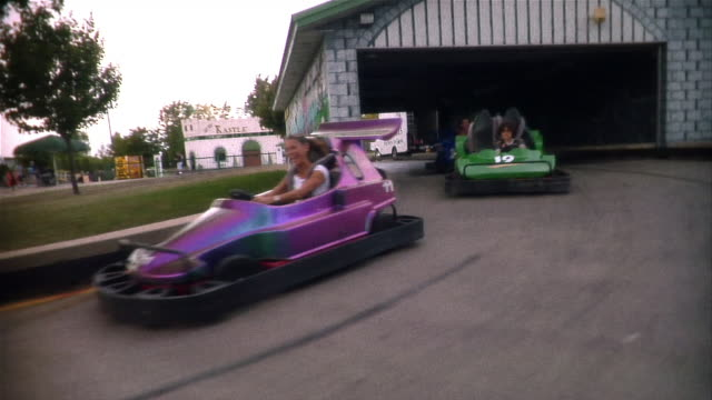 family racing go-carts through tunnel and turning around bend in track - number 3 stock videos & royalty-free footage