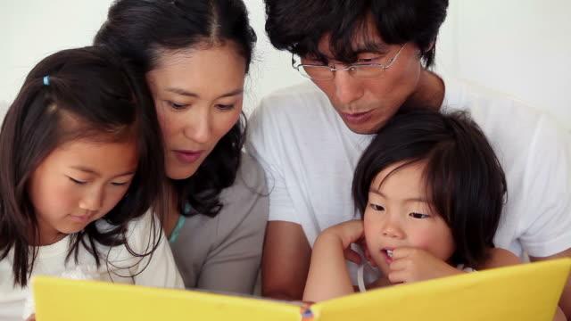 vídeos de stock, filmes e b-roll de family reading a book as they sit together - óculos de leitura