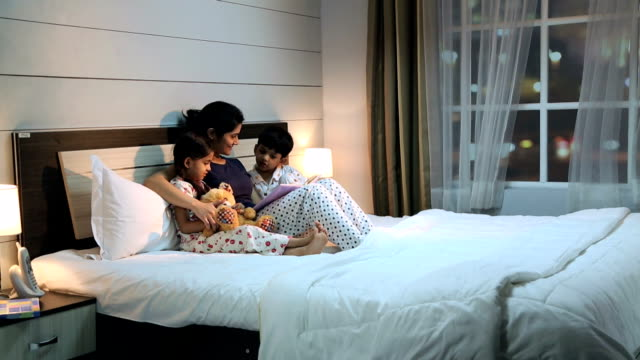 family reading book at home, delhi, india - vorlesen stock-videos und b-roll-filmmaterial