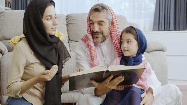 vidéos et rushes de famille lisant le livre musulman de prière avec des enfants. mode de vie au moyen-orient. - islam