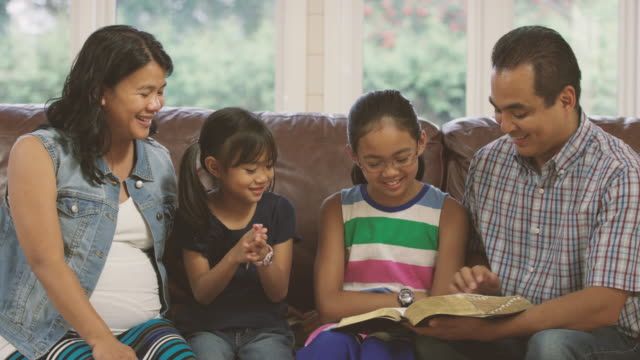Family reading the bible and praying together at home