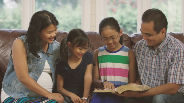 family reading the bible and praying together at home - small group of people stock videos & royalty-free footage
