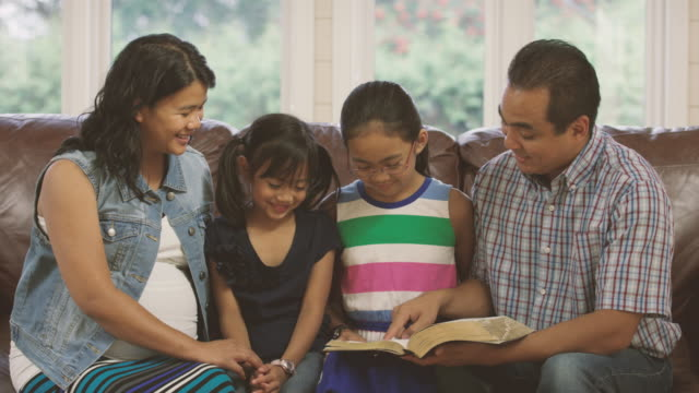 family reading the bible and praying together at home - bible stock videos & royalty-free footage