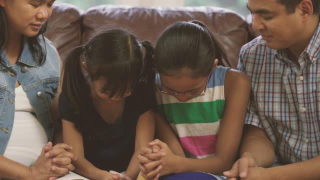 vídeos y material grabado en eventos de stock de familia leyendo la biblia y orar juntos en casa - iglesia