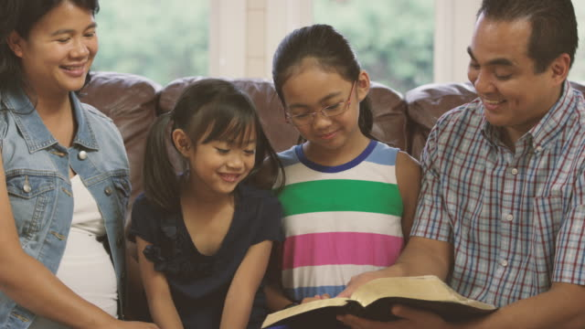 family reading the bible together - bible stock videos & royalty-free footage