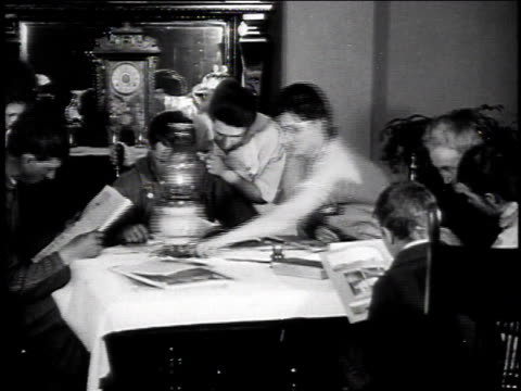 1925 ms family reads at table, man pulls lantern toward himself, and woman stands up and throws paper at him / united states - lantern stock videos & royalty-free footage
