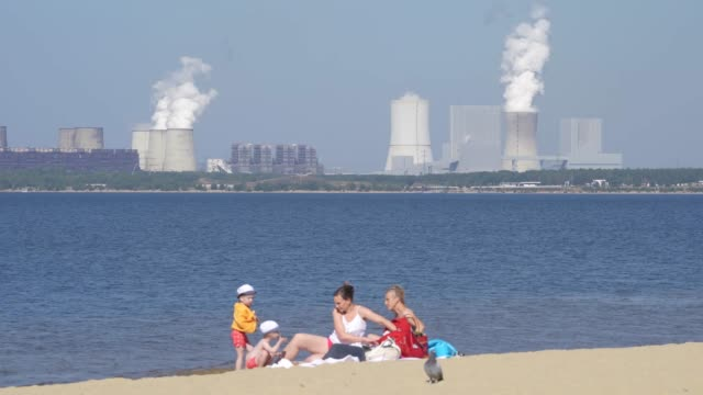 family relaxes on a beach of baerwalder see, an artificial lake created from a former open-pit coal mine, as the boxberg coal-fired power plant... - fuel and power generation stock-videos und b-roll-filmmaterial