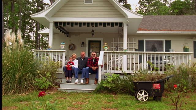 stockvideo's en b-roll-footage met a family relaxes on the front porch of a house. - gevel