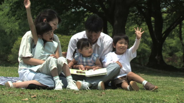 Family relaxing in park, sitting on grass