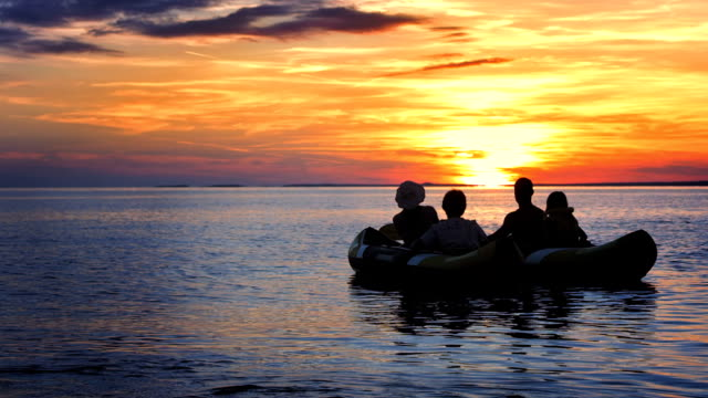 ws family relaxing in sea kayaks at sunset - canoeing stock videos & royalty-free footage