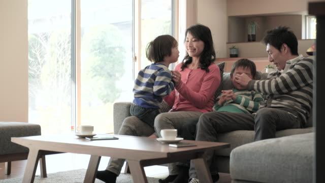 vidéos et rushes de famille détente dans le salon, canapé-lit - vie simple