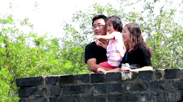 stockvideo's en b-roll-footage met family relaxing on ancient xi'an city wall. - familie met één kind
