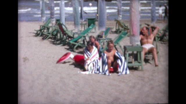 1964 family relaxing on lido beach - 水泳用浮き輪点の映像素材/bロール
