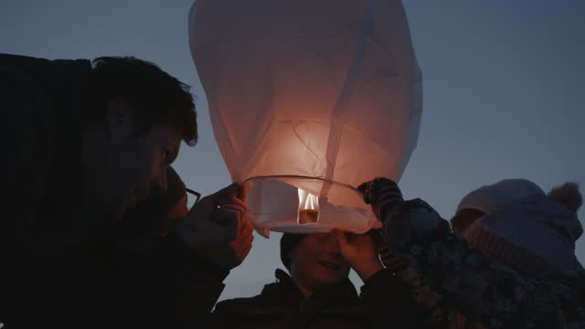 family releasing burning sky lantern - 1 minute or greater stock videos & royalty-free footage