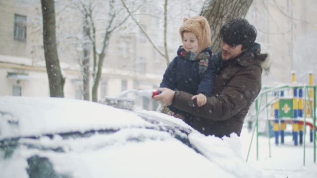 family removing snow from car in winter - winter stock videos & royalty-free footage