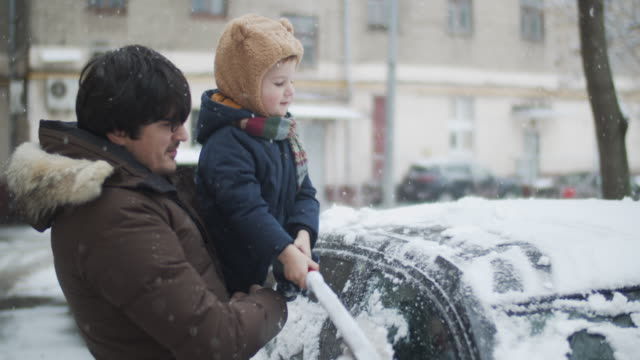 family removing snow from car in winter - mode of transport stock videos & royalty-free footage