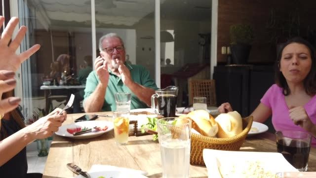 stockvideo's en b-roll-footage met familie herenigd eten barbecue - buiten de vs