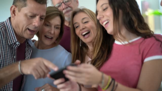 family reunited laughing at something from girl's cellphone - part of a series stock videos & royalty-free footage
