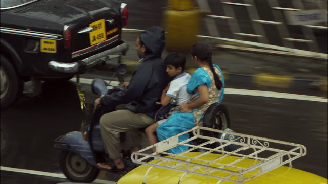 a family rides on a moped through heavy traffic in mumbai, india. available in hd. - moped stock videos and b-roll footage