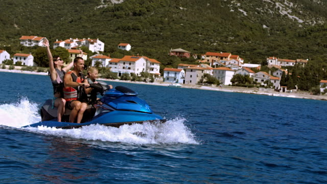 slo mo famiglia guida su una moto d'acqua lungo la costa - acquascooter video stock e b–roll