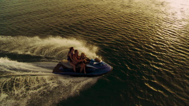Family Riding A Jet Boat At Sunset